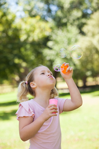 Girl blowing soap bubbles at parkの写真素材 [FYI00001382]