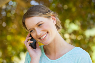 Beautiful woman using mobile phone in parkの写真素材 [FYI00001395]