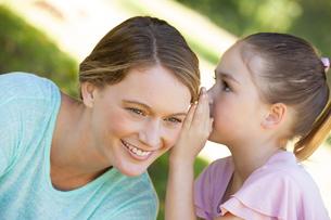 Girl whispering secret into mother's ear at parkの写真素材 [FYI00001398]