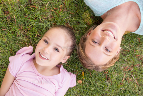 Portrait of mother and daughter lying on grass at parkの写真素材 [FYI00001405]