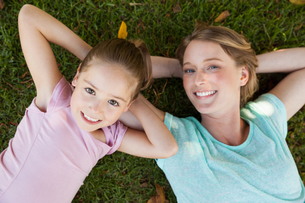 Happy mother and daughter lying on grass at parkの写真素材 [FYI00001409]