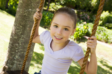 Happy young girl sitting on swing at parkの写真素材 [FYI00001411]