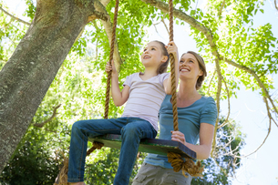 Happy mother swinging daughter at parkの写真素材 [FYI00001412]