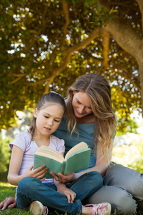 Mother and daughter reading a book at parkの写真素材 [FYI00001413]