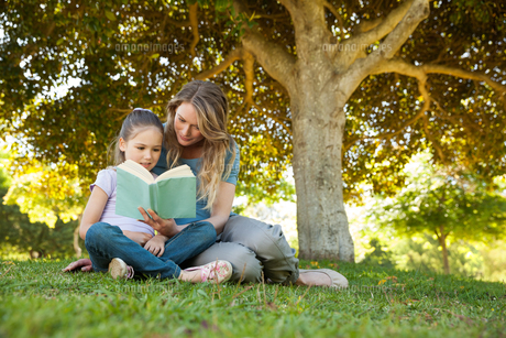 Mother and daughter reading a book at parkの写真素材 [FYI00001416]