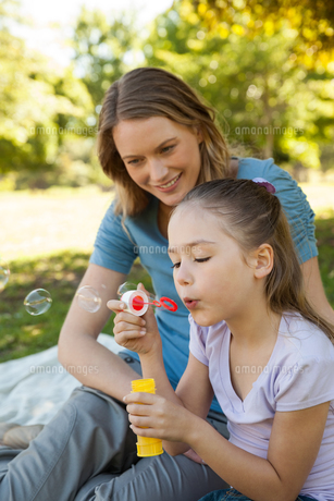 Mother with her daughter blowing soap bubbles at parkの写真素材 [FYI00001420]