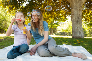 Mother with her daughter blowing soap bubbles at parkの写真素材 [FYI00001421]