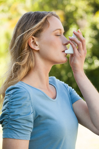 Young woman using asthma inhaler at parkの写真素材 [FYI00001437]