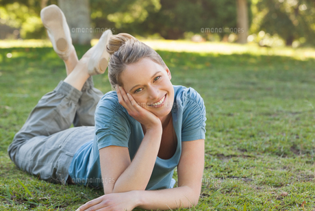 Beautiful relaxed woman lying on grass at parkの写真素材 [FYI00001438]