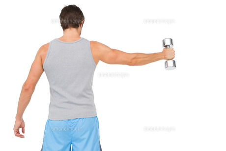 Rear view of a young man holding out dumbbellの写真素材 [FYI00001440]