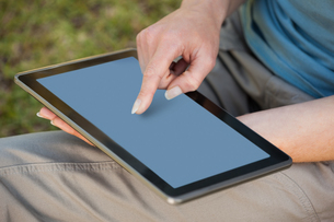 Mid section of a woman using digital tabletの素材 [FYI00001441]