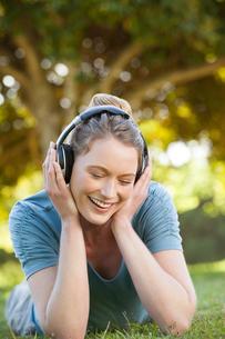 Beautiful relaxed woman enjoying music in parkの写真素材 [FYI00001442]
