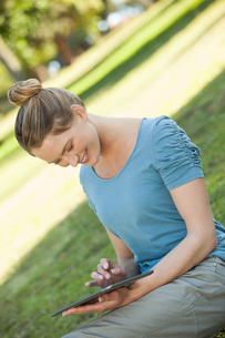 Relaxed woman using digital tablet at parkの写真素材 [FYI00001443]