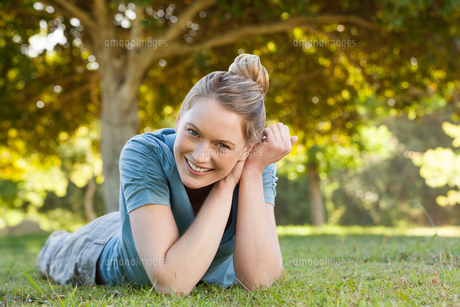 Beautiful relaxed young woman lying on grass at parkの写真素材 [FYI00001446]