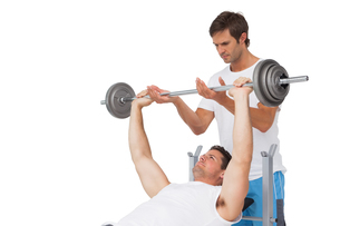 Trainer helping fit man to lift the barbell bench pressの写真素材 [FYI00001447]