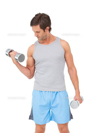 Fit young man exercising with dumbbellsの写真素材 [FYI00001448]