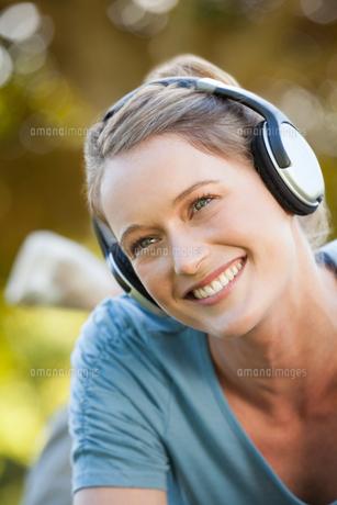 Beautiful young woman enjoying music in parkの写真素材 [FYI00001450]