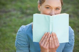Portrait of a beautiful woman with book in parkの写真素材 [FYI00001454]