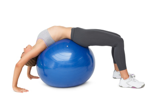 Fit young woman stretching on fitness ballの写真素材 [FYI00001464]