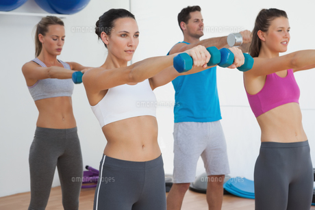 Class exercising with dumbbells in gymの写真素材 [FYI00001465]