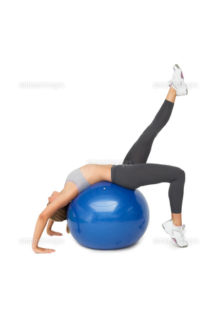 Fit young woman stretching on fitness ballの写真素材 [FYI00001468]