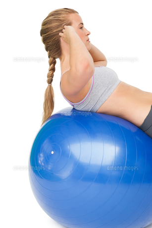 Fit young woman doing crunches on exercise ballの写真素材 [FYI00001469]