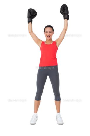 Portrait of a cheerful female boxer raising handsの写真素材 [FYI00001476]