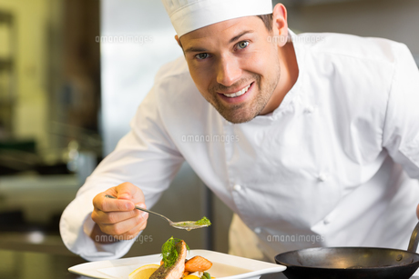 Smiling male chef garnishing food in kitchenの写真素材 [FYI00001483]