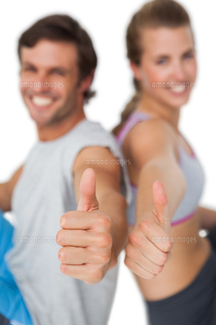Portrait of a sporty young couple gesturing thumbs upの素材 [FYI00001485]