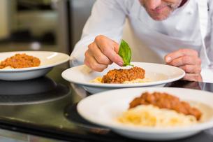 Closeup of a male chef garnishing foodの写真素材 [FYI00001491]
