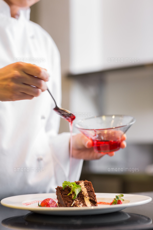 Mid section of a pastry chef decorating dessert in kitchenの写真素材 [FYI00001492]