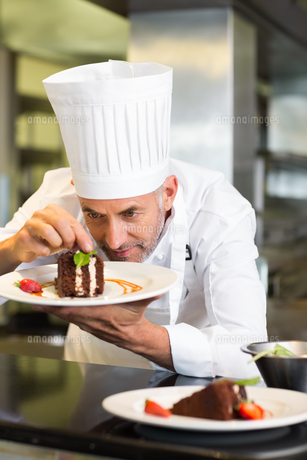 Concentrated male pastry chef decorating dessert in kitchenの写真素材 [FYI00001493]