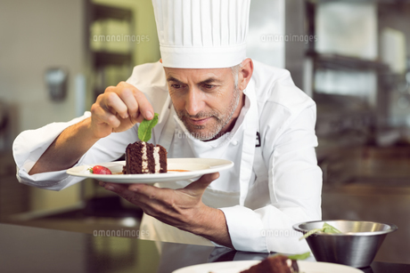Concentrated male pastry chef decorating dessert in kitchenの写真素材 [FYI00001494]