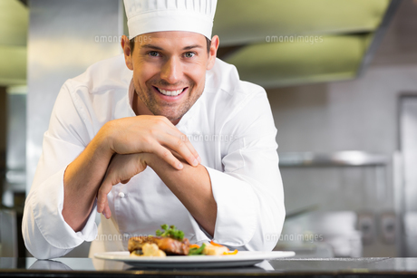Smiling male chef with cooked food in kitchenの写真素材 [FYI00001495]