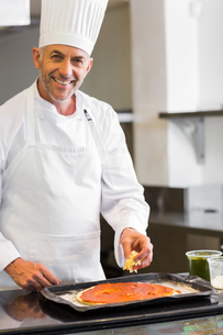 Smiling male chef garnishing food in kitchenの写真素材 [FYI00001496]