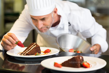 Concentrated male pastry chef decorating dessertの写真素材 [FYI00001499]