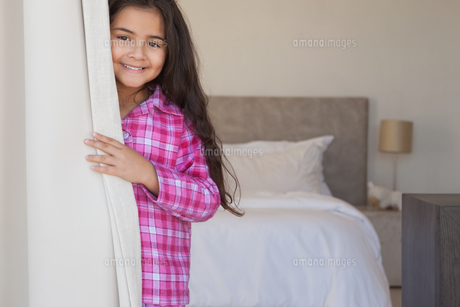 Portrait of a young smiling girl in bedroomの写真素材 [FYI00001500]