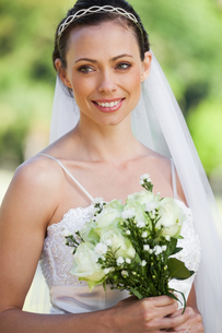 Smiling young beautiful bride with bouquet in parkの写真素材 [FYI00001501]