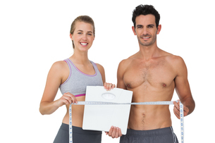 Sporty couple holding scales and measuring tapeの写真素材 [FYI00001503]