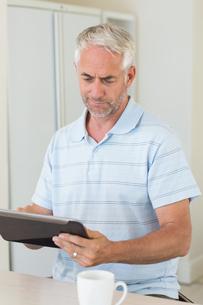 Happy man using his tablet at breakfastの写真素材 [FYI00001504]