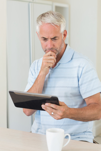 Thoughtful man using his tablet at breakfastの写真素材 [FYI00001505]