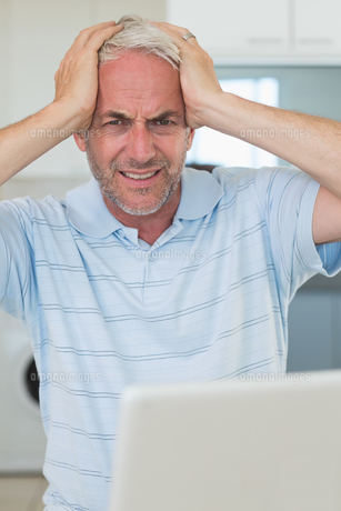 Stressed man using his laptop looking at cameraの写真素材 [FYI00001510]