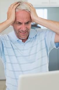 Stressed man using his laptopの写真素材 [FYI00001514]