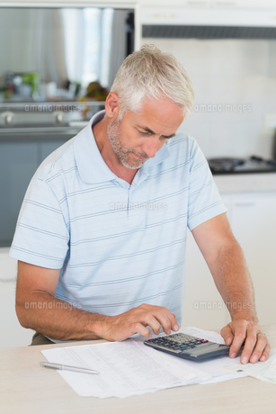 Focused man figuring out his financesの写真素材 [FYI00001517]