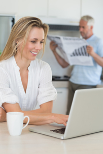 Smiling woman using laptop with partner standing with the paperの写真素材 [FYI00001519]