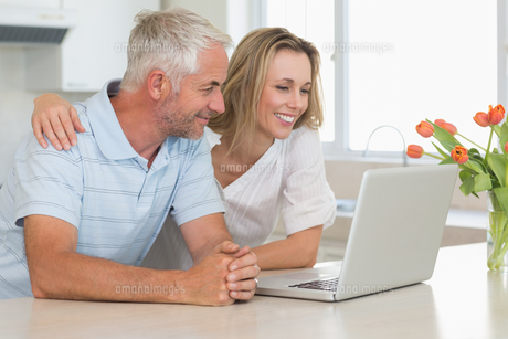 Cheerful couple using laptop together at the worktopの写真素材 [FYI00001521]