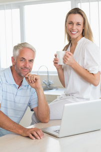 Happy couple using laptop together at the counterの写真素材 [FYI00001522]