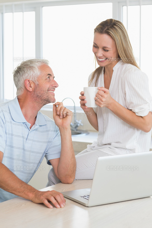 Cheerful couple using laptop together smiling at each otherの写真素材 [FYI00001524]