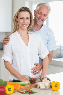 Smiling couple preparing a healthy dinner togetherの写真素材 [FYI00001530]