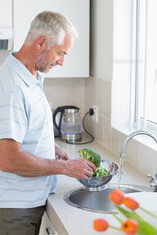 Casual man rinsing broccoli in colanderの素材 [FYI00001535]